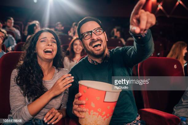 laughing couple with popcorn at cinema - comedy film stock photos and pictures