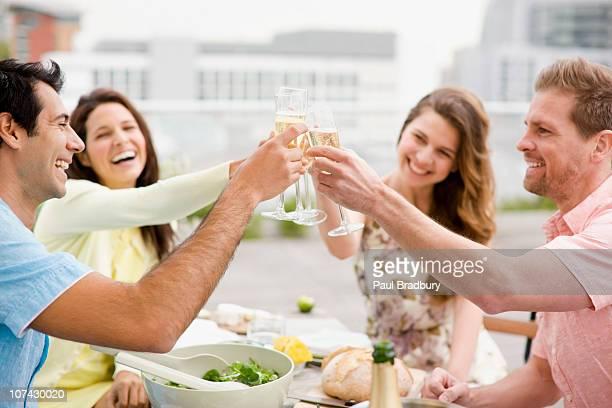 ridendo coppia brindando con champagne all'aperto - four people foto e immagini stock