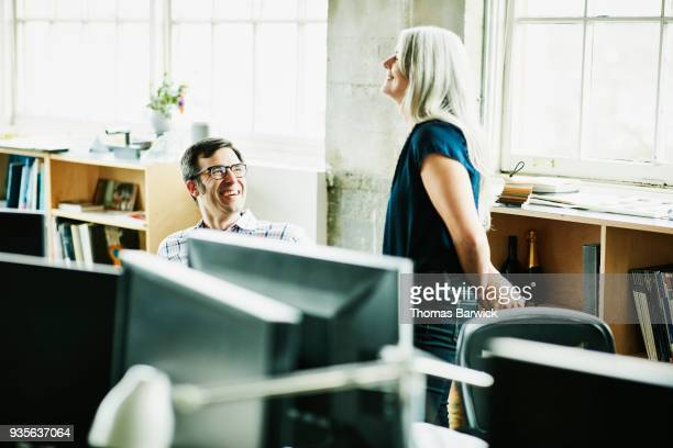 Laughing coworkers in discussion at workstation in design office
