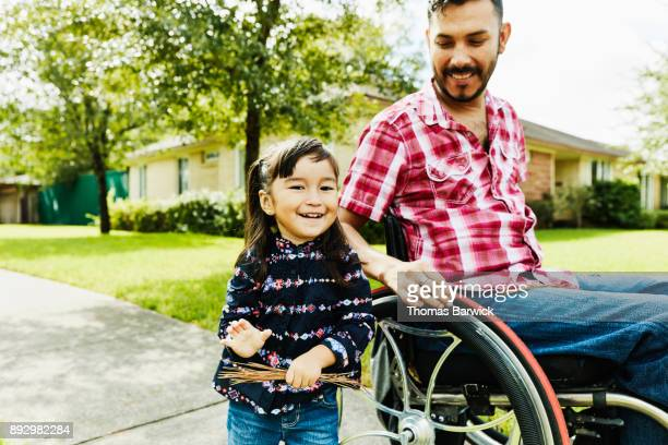 Laughing daughter out for walk through neighborhood with father in wheelchair