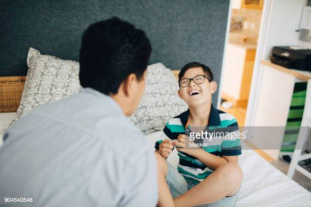 Laughing disabled boy sitting with father on bed at home