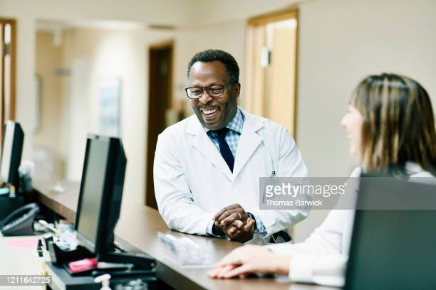 laughing doctor in discussion with colleagues in hospital - profissional da área médica imagens e fotografias de stock