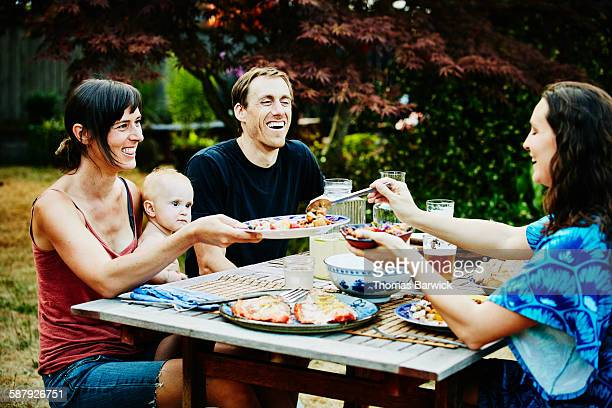 Laughing families sharing dinner in backyard