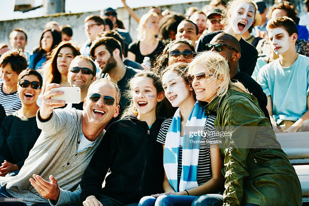 Laughing family at soccer match taking selfie : Stock Photo