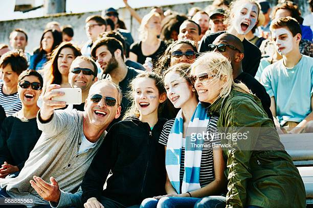 Laughing family at soccer match taking selfie