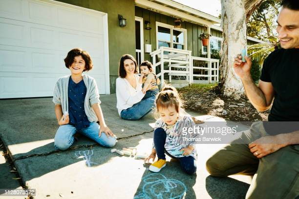 Laughing family drawing chalk pictures on driveway together on summer morning