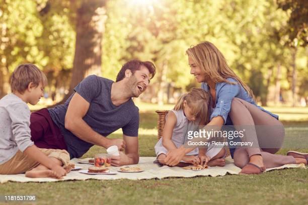 familia riendo teniendo un picnic juntos en el verano - picnic fotografías e imágenes de stock