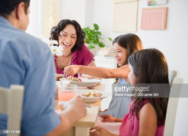 Laughing family having dinner together