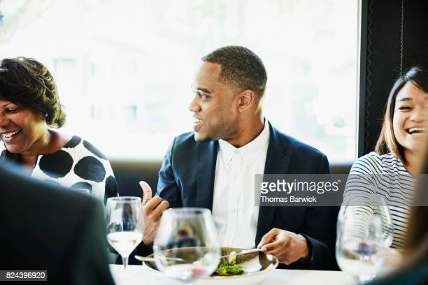 Laughing family in discussion while sharing a meal in restaurant