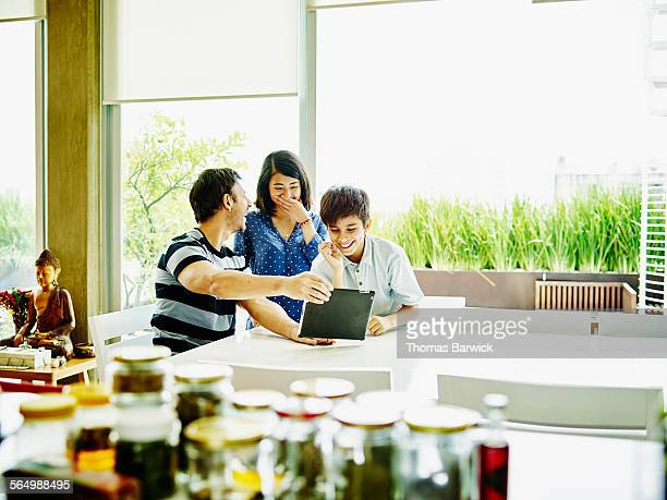 Laughing family looking at digital tablet