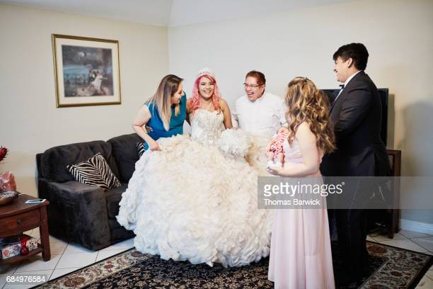Laughing family members in living room with young woman dressed in quinceanera gown