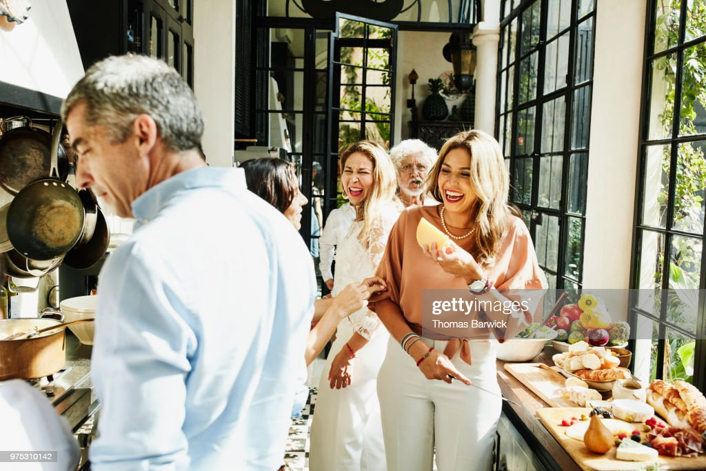 Laughing family members preparing food in kitchen for celebration dinner : Stock Photo