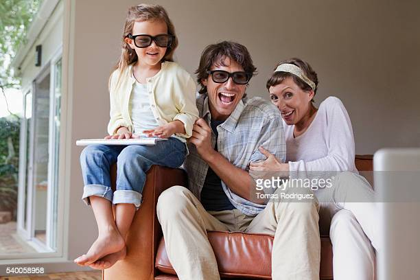 Laughing family on sofa wearing 3D glasses