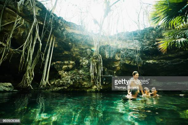 Laughing family playing together while swimming in cenote during vacation