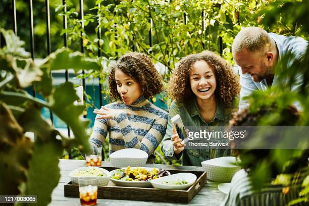 laughing family playing with photos on smart phones during backyard picnic - black hair stock pictures, royalty-free photos & images