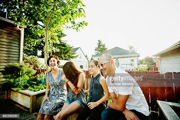 Laughing family sitting together in garden of home