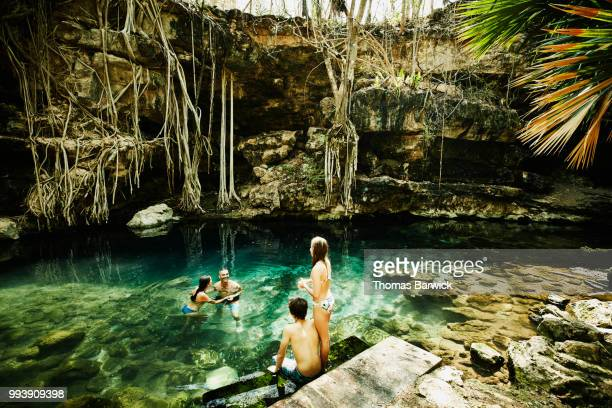 Laughing family swimming and exploring cenote during vacation