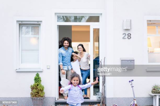 laughing family waiting at the entrance of their home - 建物入口 ストックフォトと画像