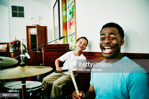 Laughing father and son playing on drum set