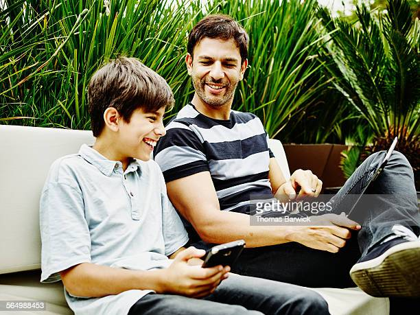 Laughing father and son sitting together on patio