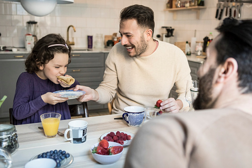 Laughing father holding plate while daughter eating pancake at table - gettyimageskorea