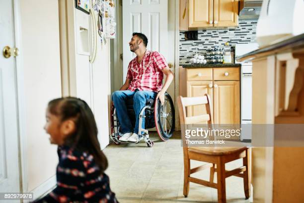Laughing father in wheelchair preparing meal while daughter runs through kitchen