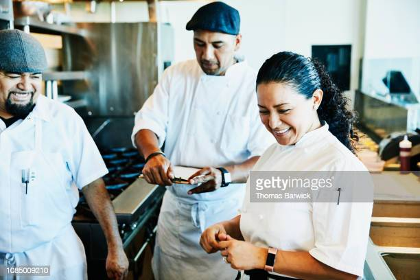 laughing female chef reviewing plans for dinner service with kitchen staff - schwarzes haar stock-fotos und bilder