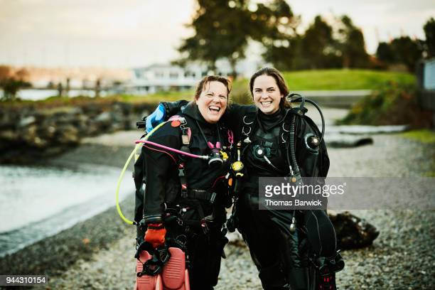 Laughing female dive partners standing together on beach after open water dive