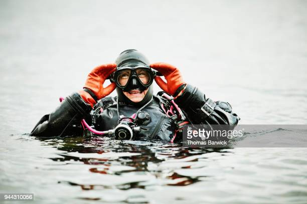 Laughing female diver adjusting mask before descending in open water dive