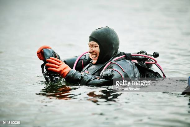 Laughing female diver putting on mask in water before open water dive