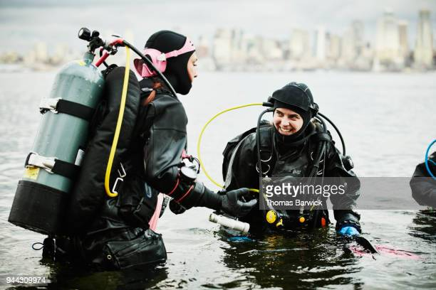 Laughing female divers entering the water for open water dive