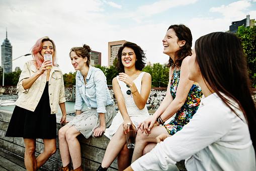 Laughing female friends having drinks on deck - gettyimageskorea