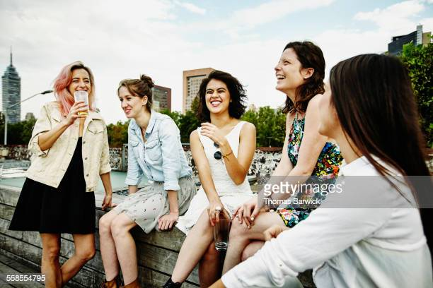 Laughing female friends having drinks on deck