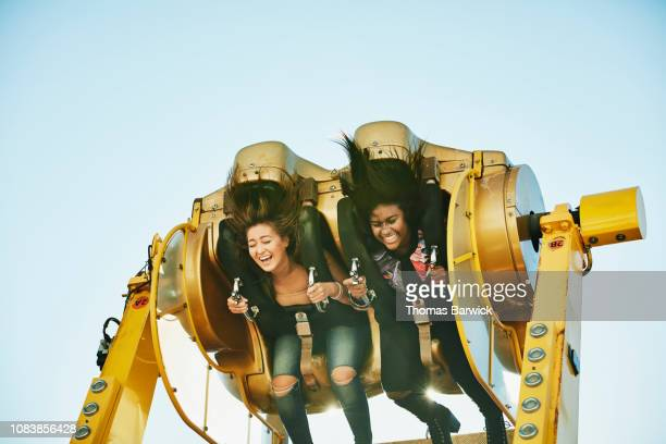 laughing female friends spinning upside down on amusement park ride - (position) stock pictures, royalty-free photos & images