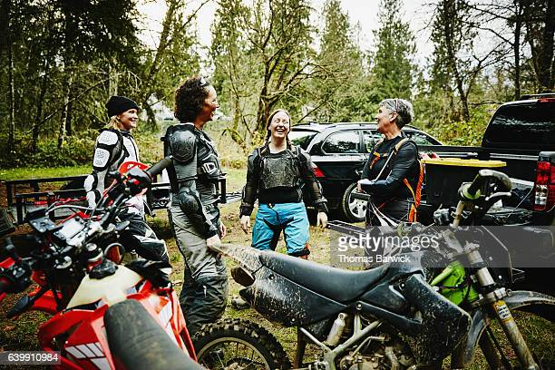 Laughing female motorcyclists hanging out after riding dirt bikes together