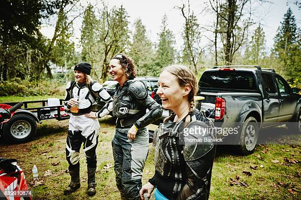Laughing female motorcyclists hanging out together after riding dirt bikes