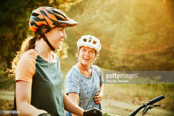 laughing female mountain bikers in discussion while resting during ride - riding stock pictures, royalty-free photos & images