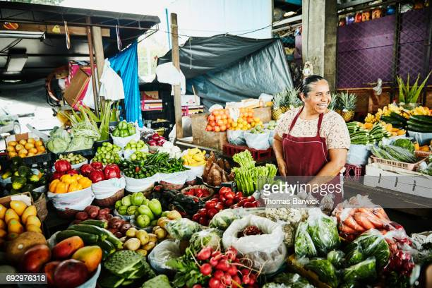 laughing female produce vendor working at stand in marketplace - markt stockfoto's en -beelden