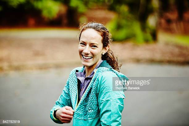 laughing female runner zipping up jacket - ファスナー ストックフォトと画像