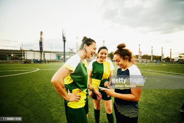 laughing female soccer players looking at smart phone after game - only mid adult women stock pictures, royalty-free photos & images