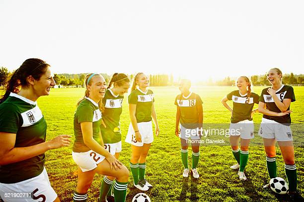 Laughing female soccer teammates on field