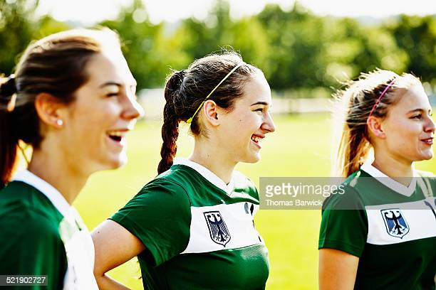 Laughing female soccer teammates together on field