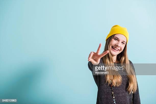 laughing female teenager showing victory-sign wearing yellow cap - 16 17 jaar stockfoto's en -beelden