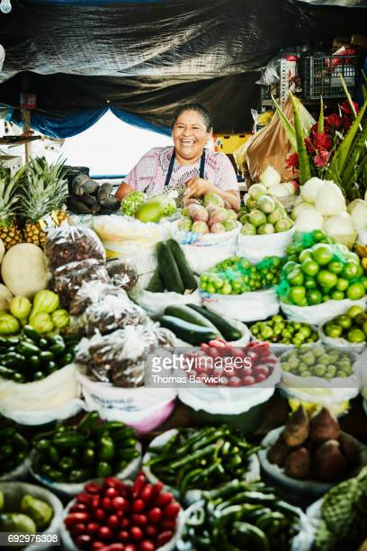 Laughing female vendor preparing produce at stand in marketplace