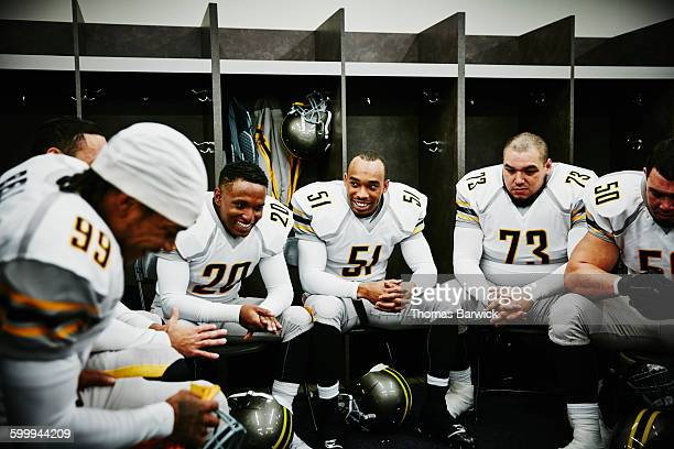 laughing football players in locker room - american football team stock pictures, royalty-free photos & images
