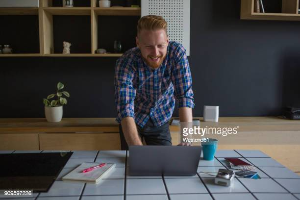 Laughing freelance businessman working on his laptop at home