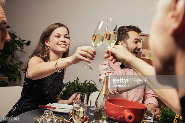 Laughing friends clinking glasses with champagne at New Year's Eve