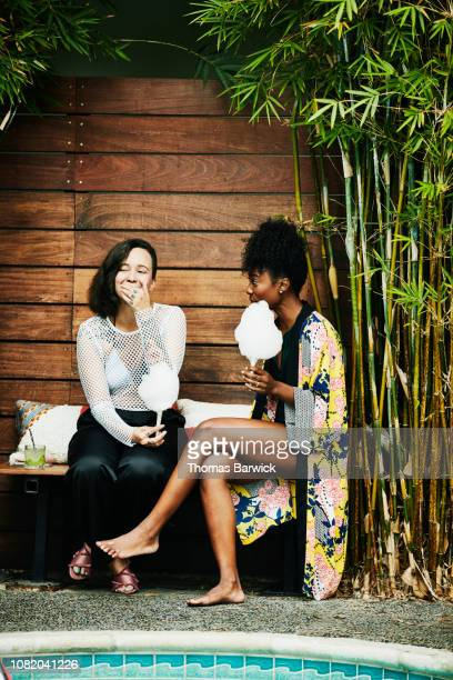 laughing friends eating cotton candy while sitting beside hotel pool during party - rumor stock pictures, royalty-free photos & images
