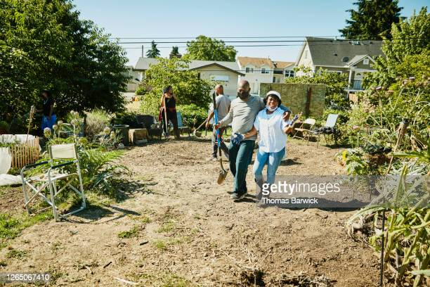 laughing friends embracing while volunteering together on urban farm - self sufficiency stock pictures, royalty-free photos & images
