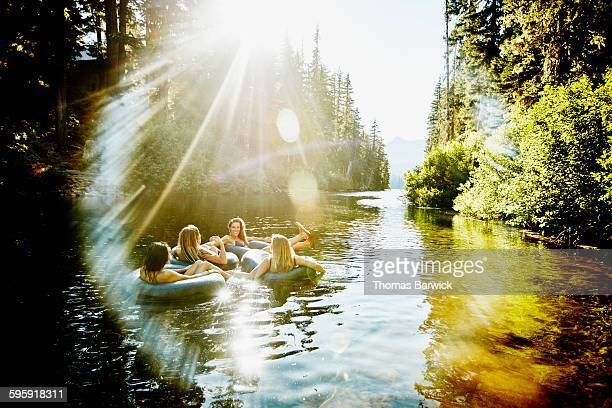 laughing friends floating on river in inner tubes - soleggiato foto e immagini stock